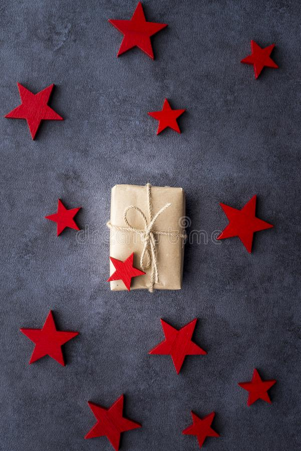 Christmas present in decorative box and red wooden stars on a dark background stock image