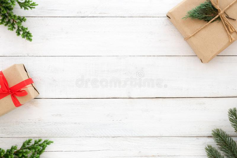 Christmas present gift boxes and fir leaves decoration rustic elements on white wood background stock images