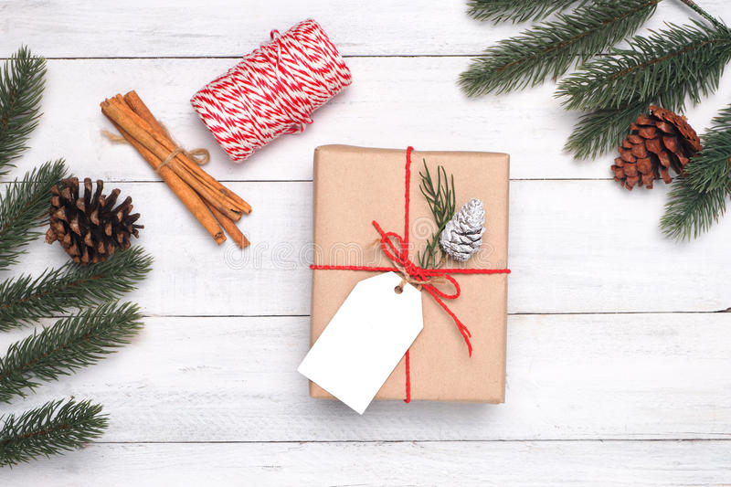 Christmas present gifts box, fir leaves, pine cone, and rustic decoration on vintage wooden background. royalty free stock photos