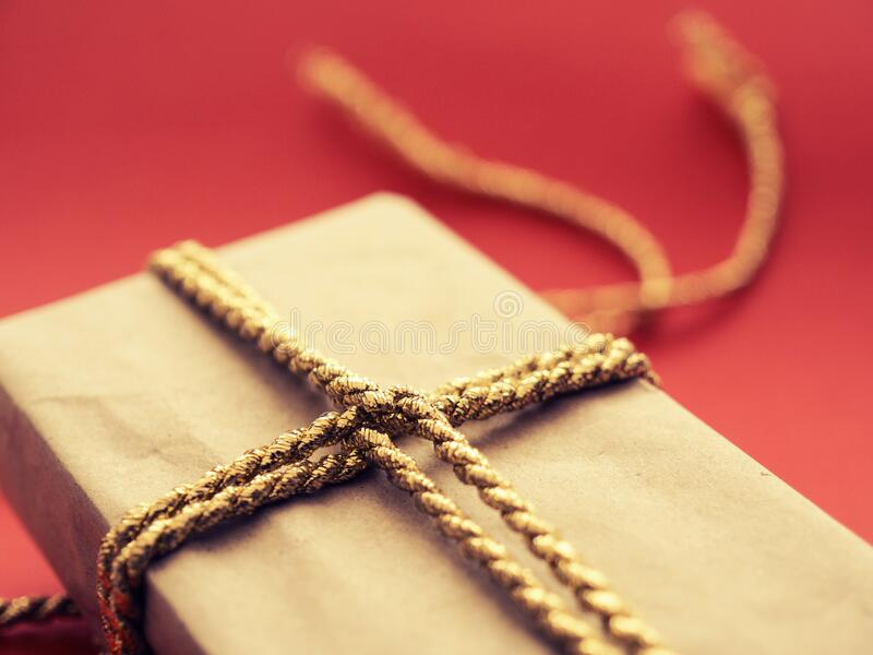 A Christmas present with golden gift bank on a red background royalty free stock image