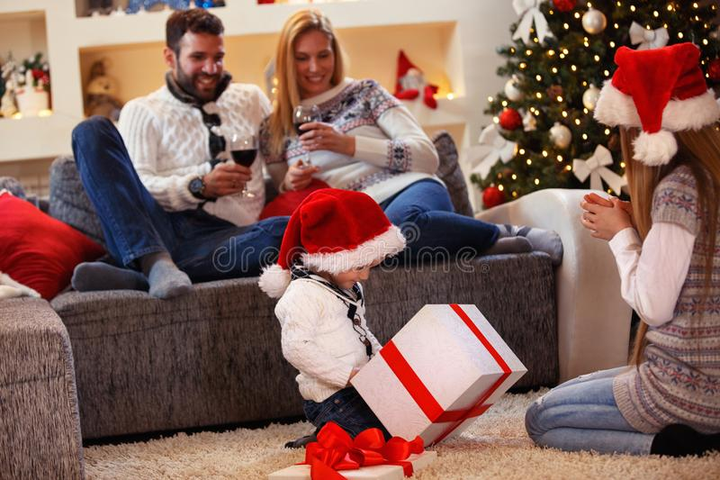 Christmas present - children opens present with family. Christmas present - happy children opens present with family stock image