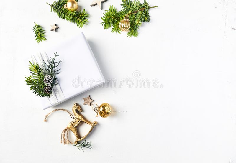 Christmas present, vintage decorations and fir twigs on white wooden background. royalty free stock images