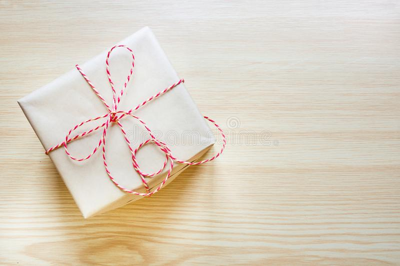 Christmas present wrapped in craft paper with ribbon on wooden board. Top view. Christmas present wrapped in craft paper with ribbon on wooden board. Top view royalty free stock photography