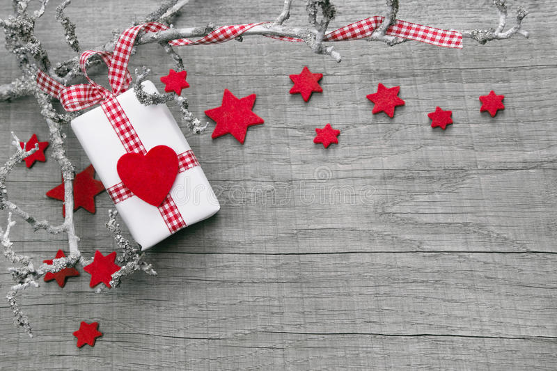 Christmas present wrapped in red paper on a wooden background stock image