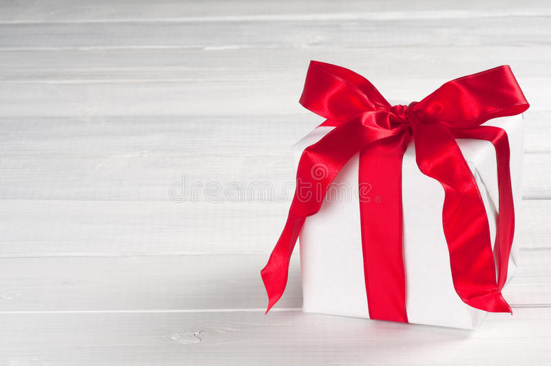 Christmas Present Wrapped in White Paper with Red Satin Ribbon on gray and white board background with room for text. Horizontal of a white Christmas present stock photography