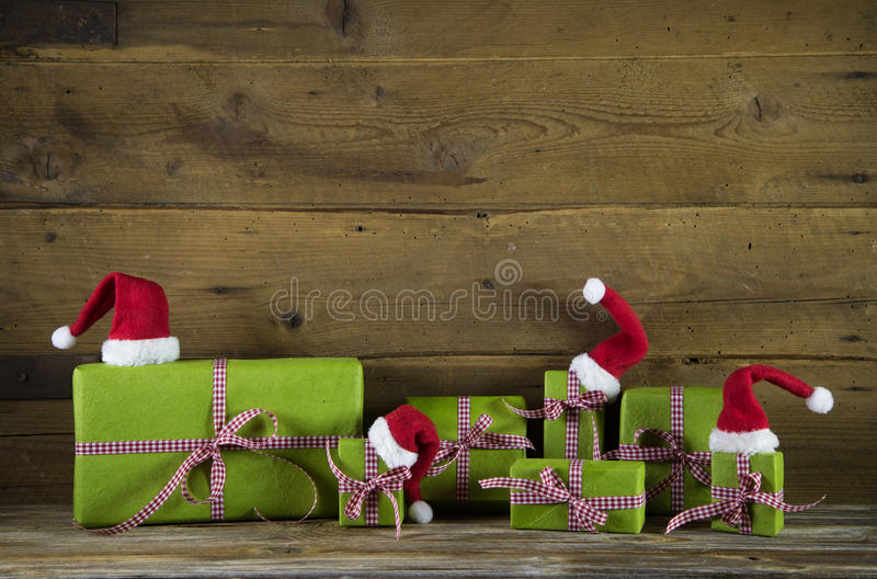 Christmas presents in apple green decorated with red santa hats. On wooden rustic background. Idea for a gift certificate royalty free stock image