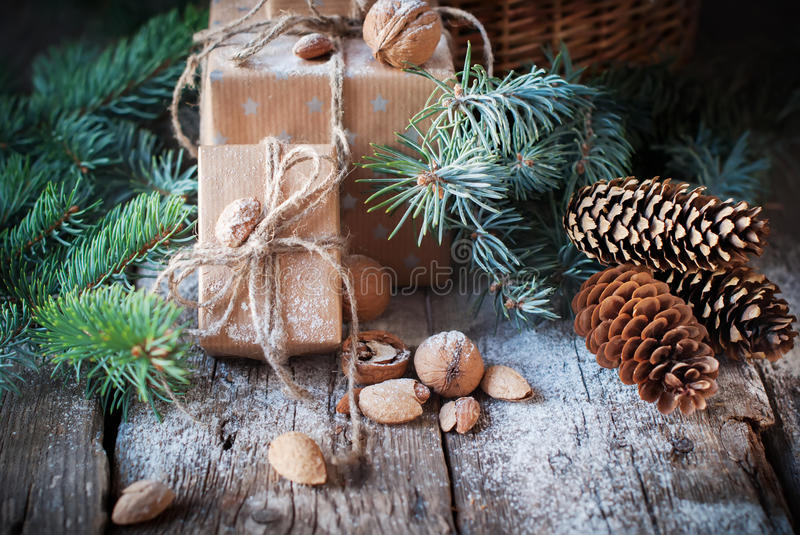 Christmas Presents Boxes Decorated with Cord, Coniferous, Pine Cones, Walnuts, Almonds on Wooden Background royalty free stock photos