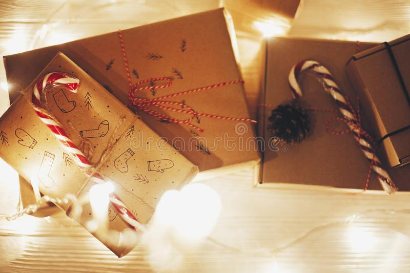 Christmas presents with candy in lights in evening festive room in warm illumination, top view. space for text. modern craft gifts. Flat lay. merry christmas stock image