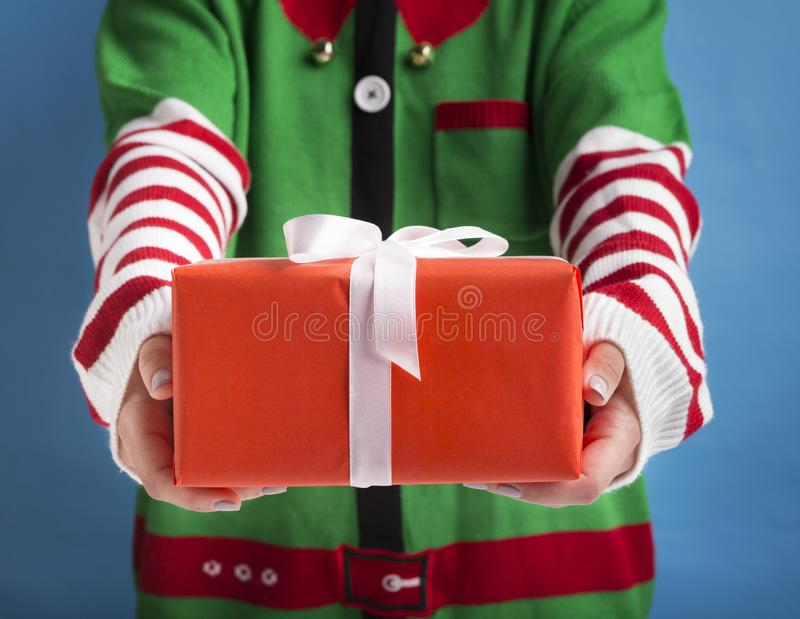 Santa`s little helper holding holiday gift with ribbon on background royalty free stock image