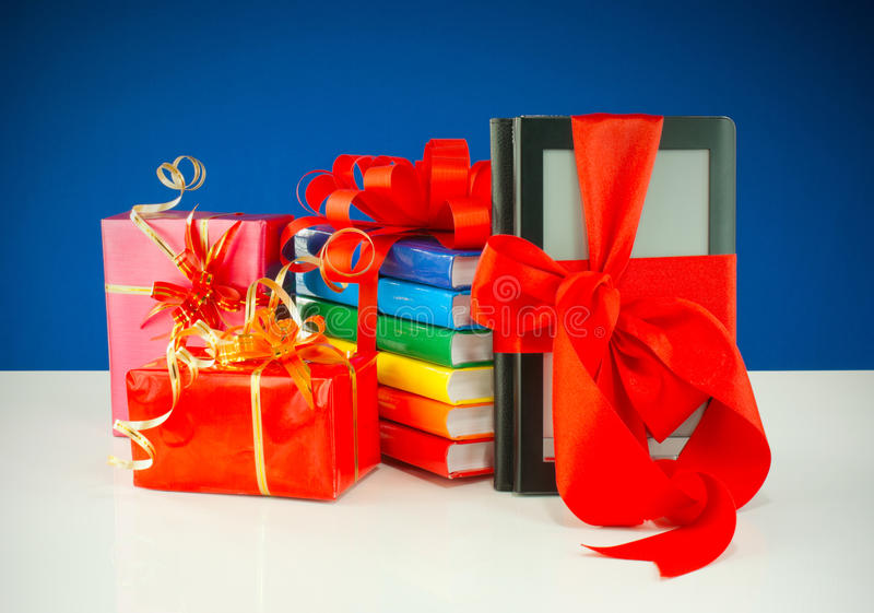 Christmas presents with electronic book reader. Against blue background stock images