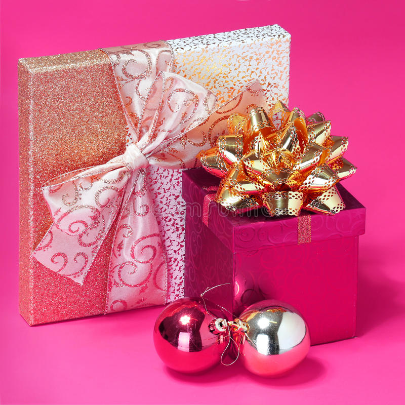Christmas Presents. Gift Boxes with Gold Bow. And Shiny Christmas Balls over Hot Pink background royalty free stock image