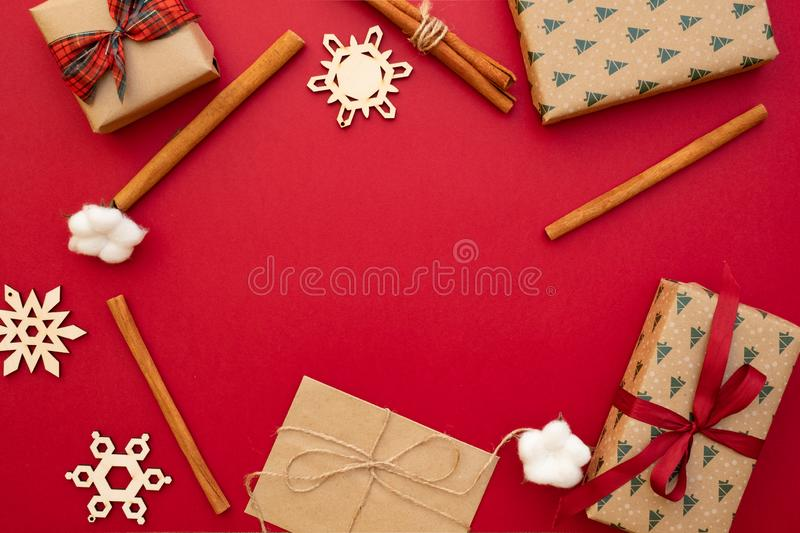 Christmas presents. Gifts packed in craft paper, decorative snowflakes, twine, cinnamon sticks on red background. Xmas and Happy N royalty free stock image