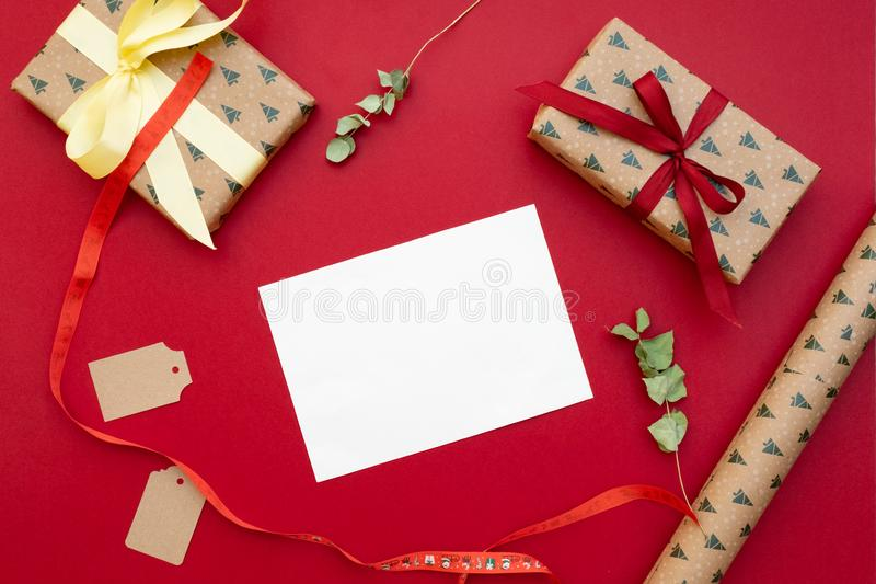 Christmas presents. Gifts packed in craft paper, greeting card letter, bow, dried flowers on red background. Xmas and Happy New Ye royalty free stock photography