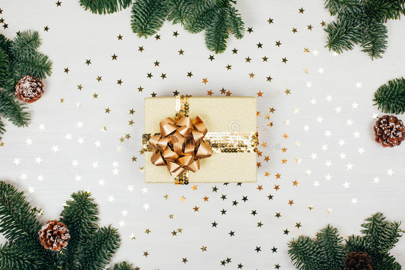 Christmas presents with golden ribbon. On white wooden background in a frame made of fir branches with canes. Flat lay, rustic style stock photo