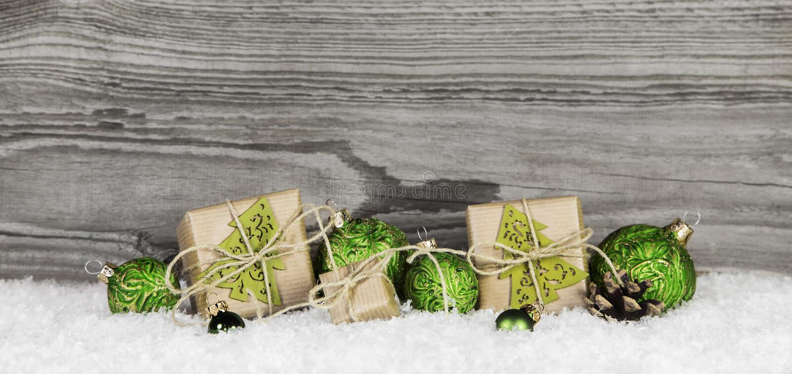 Christmas presents and green balls on wooden old grey background stock photo