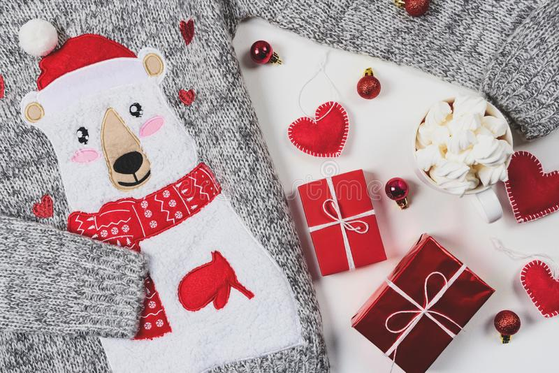 Christmas presents. Knitted sweater, slippers, gift boxes, chocolate muffins and hot chocolate with marshmallow. Laid on a white wooden table background. Flat stock photos