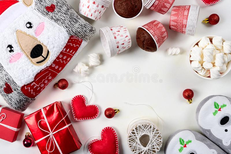 Christmas presents. Knitted sweater, slippers, gift boxes, chocolate muffins and hot chocolate with marshmallow. Laid on a white wooden table background. Flat stock images