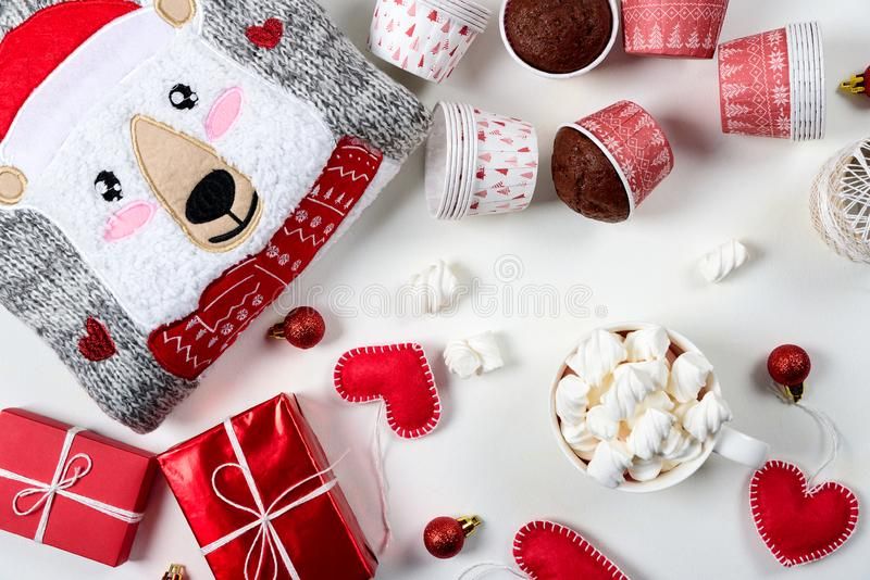 Christmas presents. Knitted sweater, slippers, gift boxes, chocolate muffins and hot chocolate with marshmallow. Laid on a white wooden table background. Flat royalty free stock photos