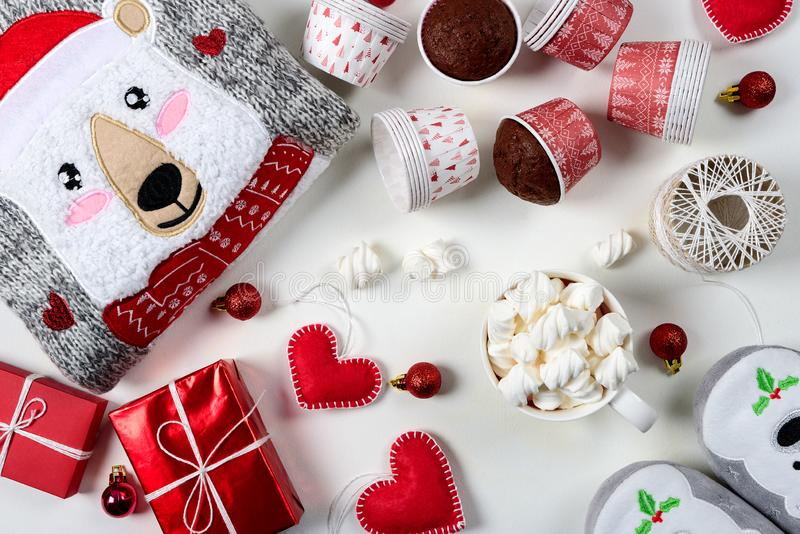 Christmas presents. Knitted sweater, slippers, gift boxes, chocolate muffins and hot chocolate with marshmallow. Laid on a white wooden table background. Flat royalty free stock photography