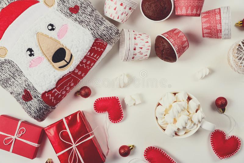 Christmas presents. Knitted sweater, slippers, gift boxes, chocolate muffins and hot chocolate with marshmallow. Laid on a white wooden table background. Flat stock photo