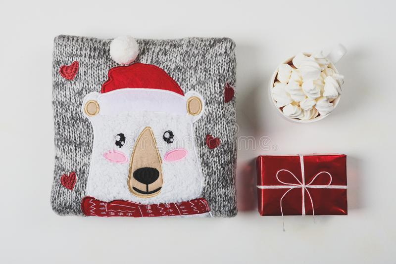 Christmas presents. Knitted sweater, slippers and hot chocolate with marshmallow laid on a white wooden table background. Flat lay. Top view. Toned stock photography