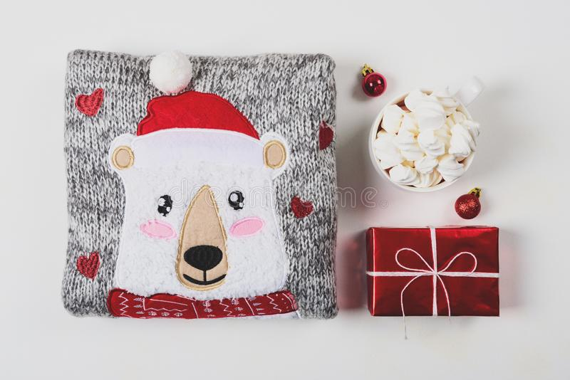 Christmas presents. Knitted sweater, slippers and hot chocolate with marshmallow laid on a white wooden table background. Flat lay. Top view. Toned royalty free stock image