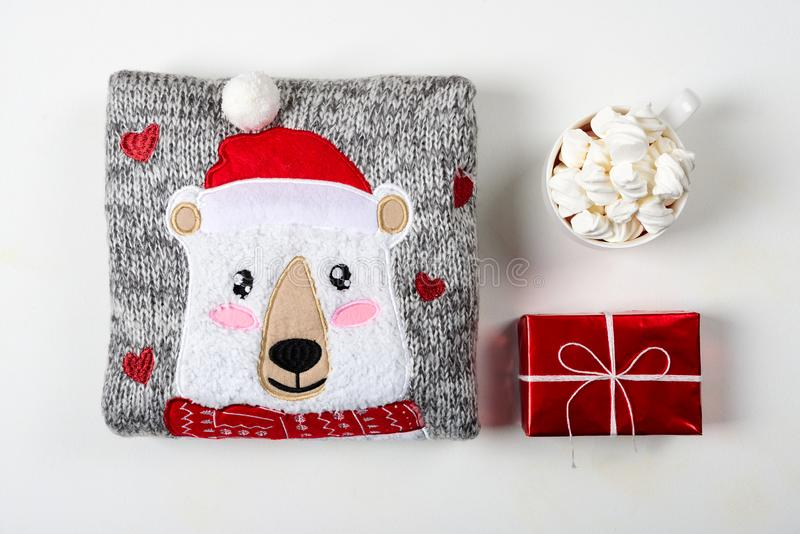 Christmas presents. Knitted sweater, slippers and hot chocolate with marshmallow laid on a white wooden table background. Flat lay. Top view stock photography