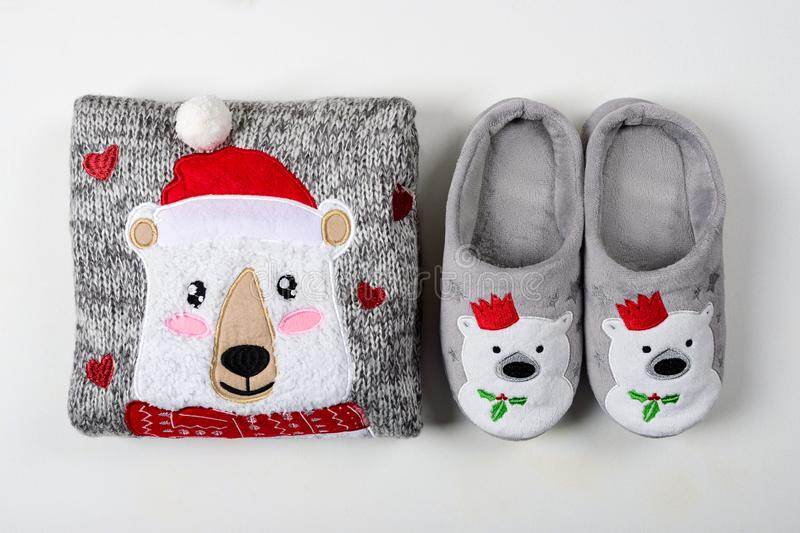 Christmas presents. Knitted sweater, slippers and hot chocolate with marshmallow laid on a white wooden table background. Flat lay. Top view stock photo