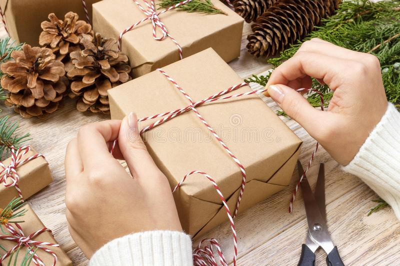 Christmas presents preparation. Gift box wrapped in black and white striped paper, a crate full of pine cones and christmas toys a stock photo