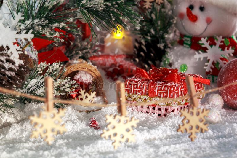 Christmas presents in the snow, snowflakes on clothespins, cheerful snowman and red lantern on the background of New Year`s scener royalty free stock photo