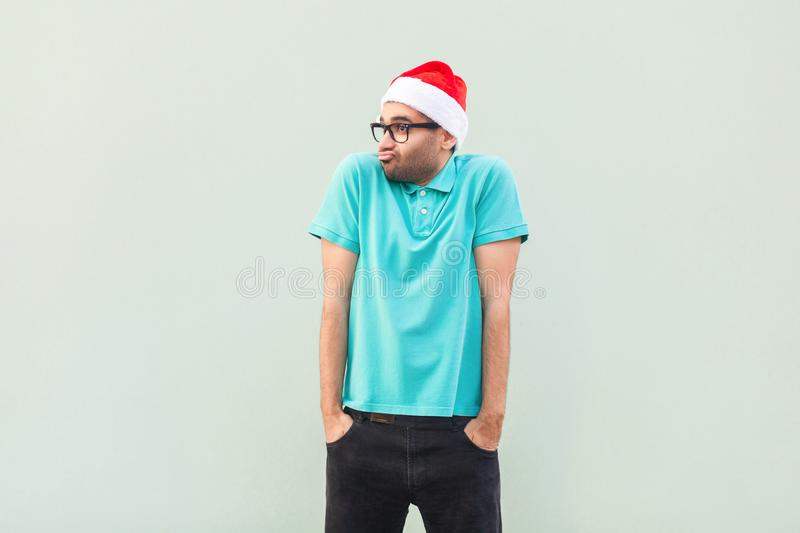 Christmas problem. Flying of thoughts. Thoughtful bearded businessman looking away while standing against gray wall. stock image