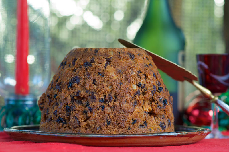 Christmas Pudding. Homemade Christmas pudding on a plate with red and green festive background stock image