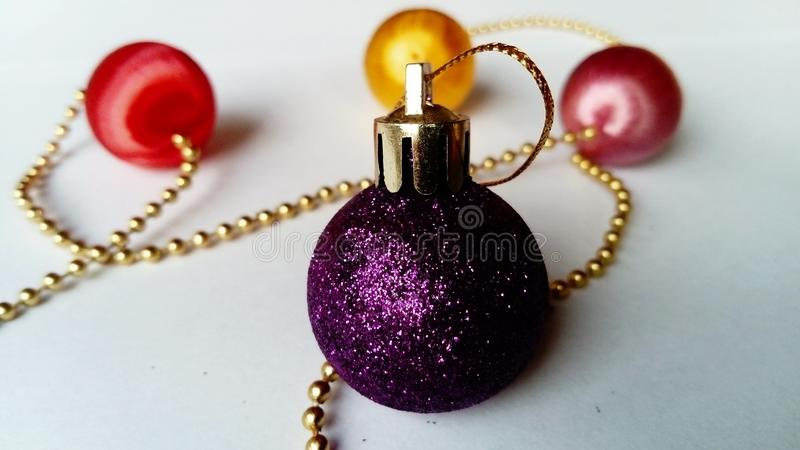 Christmas purple ball with sparkles to decorate the holiday tree. Gold threads, red, pink and yellow balls on the back white stock image