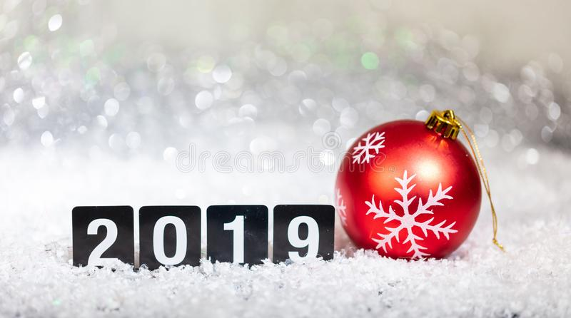 Christmas red ball and new year 2019, on snow, abstract bokeh lights background. Copy space stock images