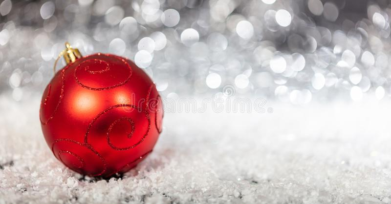 Christmas red ball and snow, abstract bokeh lights background royalty free stock photos