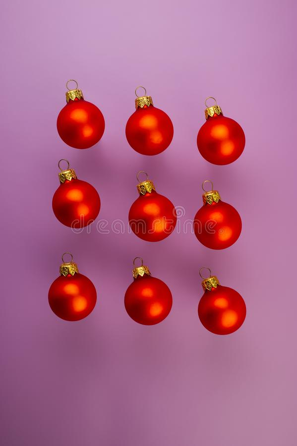 Christmas red balls lie on a purple background. Christmas composition, winter season stock images