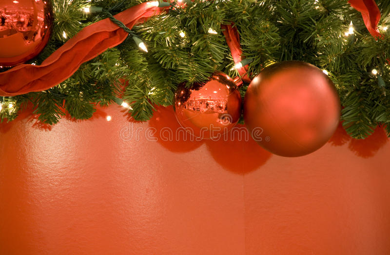 Christmas red balls lights tree background. Christmas decoration with red balls, lights, ribbon tree and red background royalty free stock images