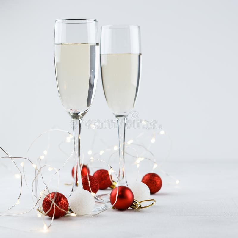 Christmas red balls and two glasses of champagne. Composition for Christmas with red and white balls, white lights and two glasses of champagne stock image