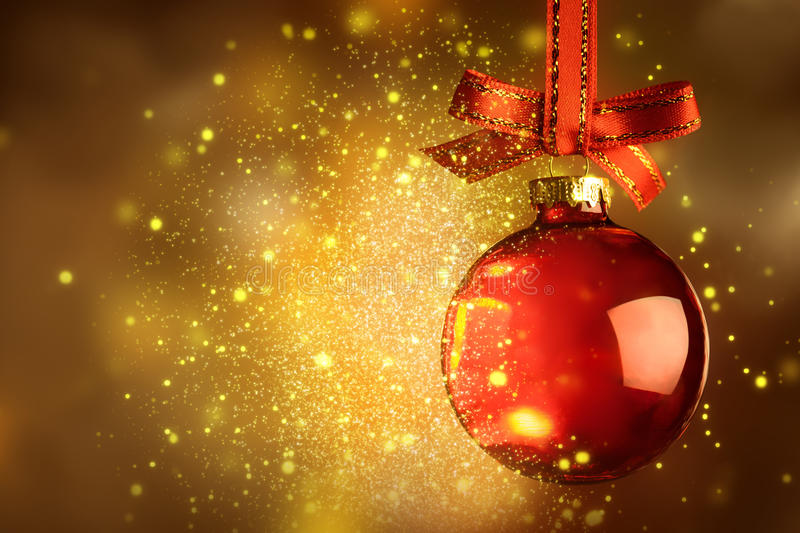Christmas red bauble with sparkle over magic glitter shiny background royalty free stock images