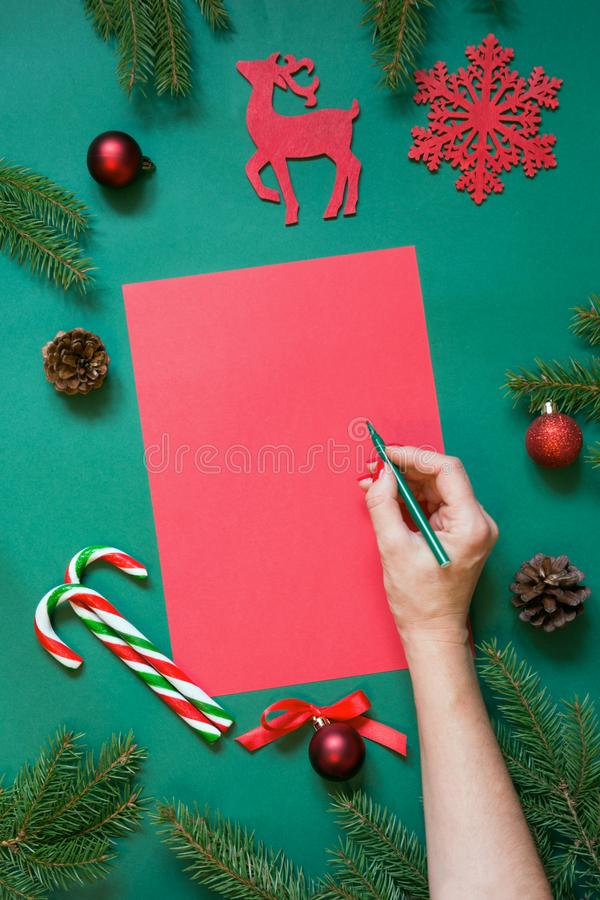 Christmas red blank for letter to Santa or your wishlist or advent activities on green. Female hand writing. Top view. Flat lay royalty free stock photography
