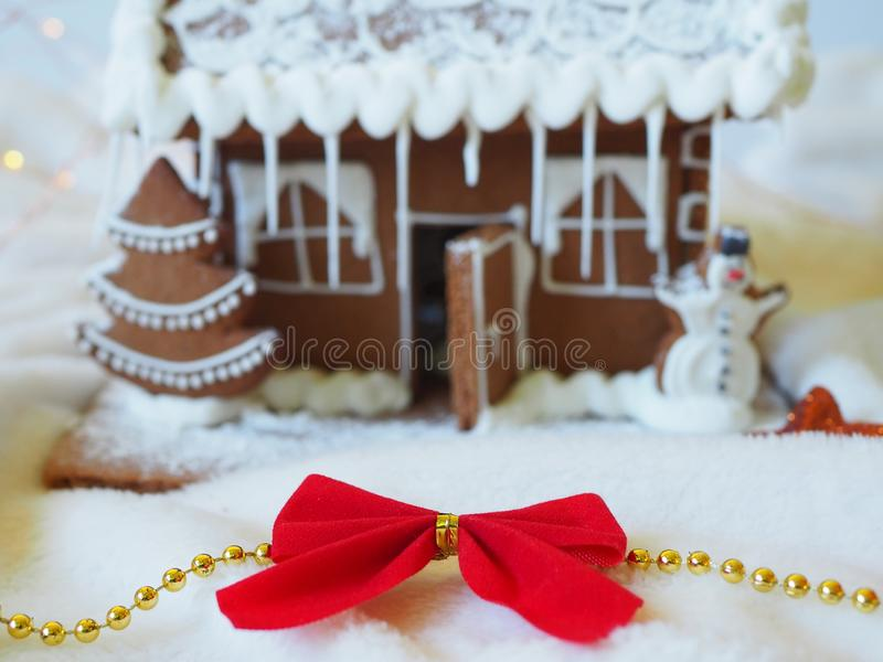 Christmas red bow in front of a gingerbread house in the background. Christmas scenery, beautiful decoration stock image