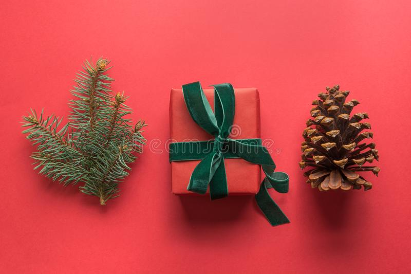 Christmas red collection with gift, pine cone, evergreen branches on red. Flat lay. View from above royalty free stock photography