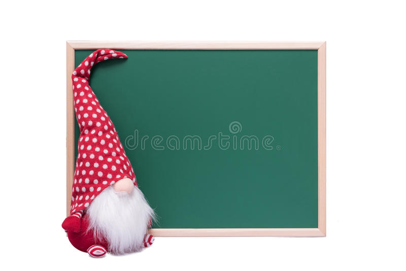 Christmas Red Elf With Long White Beard Sitting Beside an Empty. Green Chalkboard on a White Background royalty free stock photos