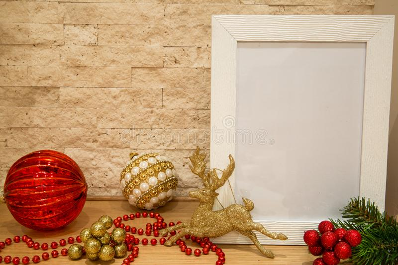 Christmas red glass balls and balls with white and golden pearls. Red beads, sparkle golden deer and fir tree branches with red and golden winter berries. Mock stock photos