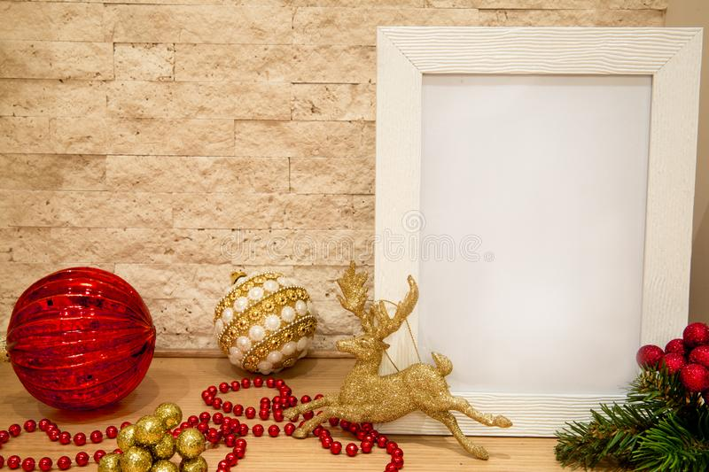 Christmas red glass balls and balls with white and golden pearls. Red beads, sparkle golden deer and fir tree branches with red and golden winter berries. Mock stock image