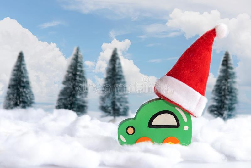 Christmas red hat on wood toy car on the snow. Christmas holiday celebration concept stock images
