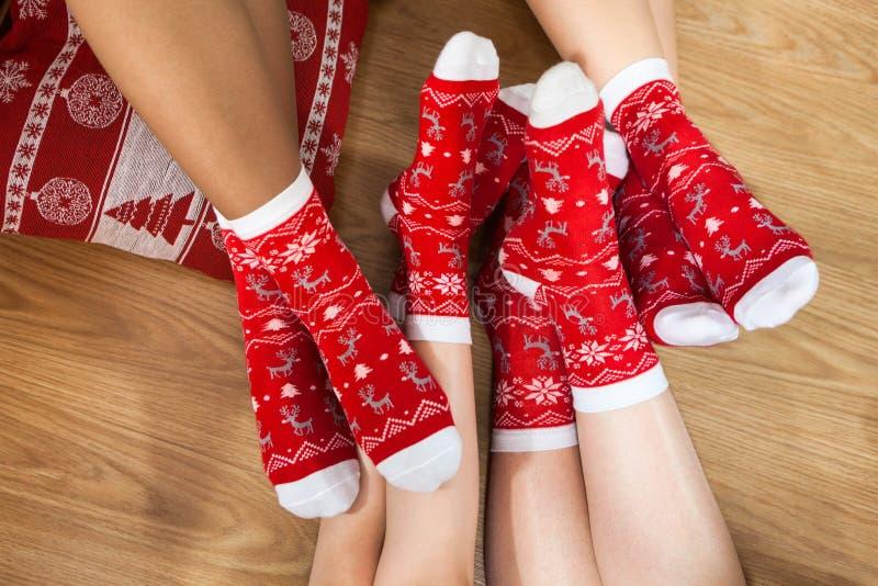 Christmas socks on feet of family. Legs crossing on floor. Christmas red socks on feet of family. Legs crossing on floor stock image