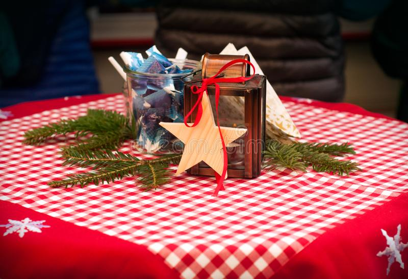 Christmas, red tablecloth with stars. wooden star, sugar, and container for candle royalty free stock photography