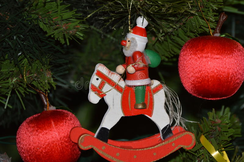 Christmas red wooden man on horse and red globes decoration stock photography