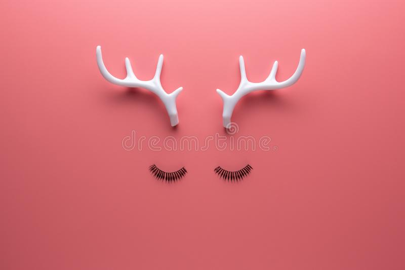 Christmas reindeer face made of eyelashes and white antlers on pink background. Minimal New Year or Christmas concept. Flat lay.  royalty free stock images